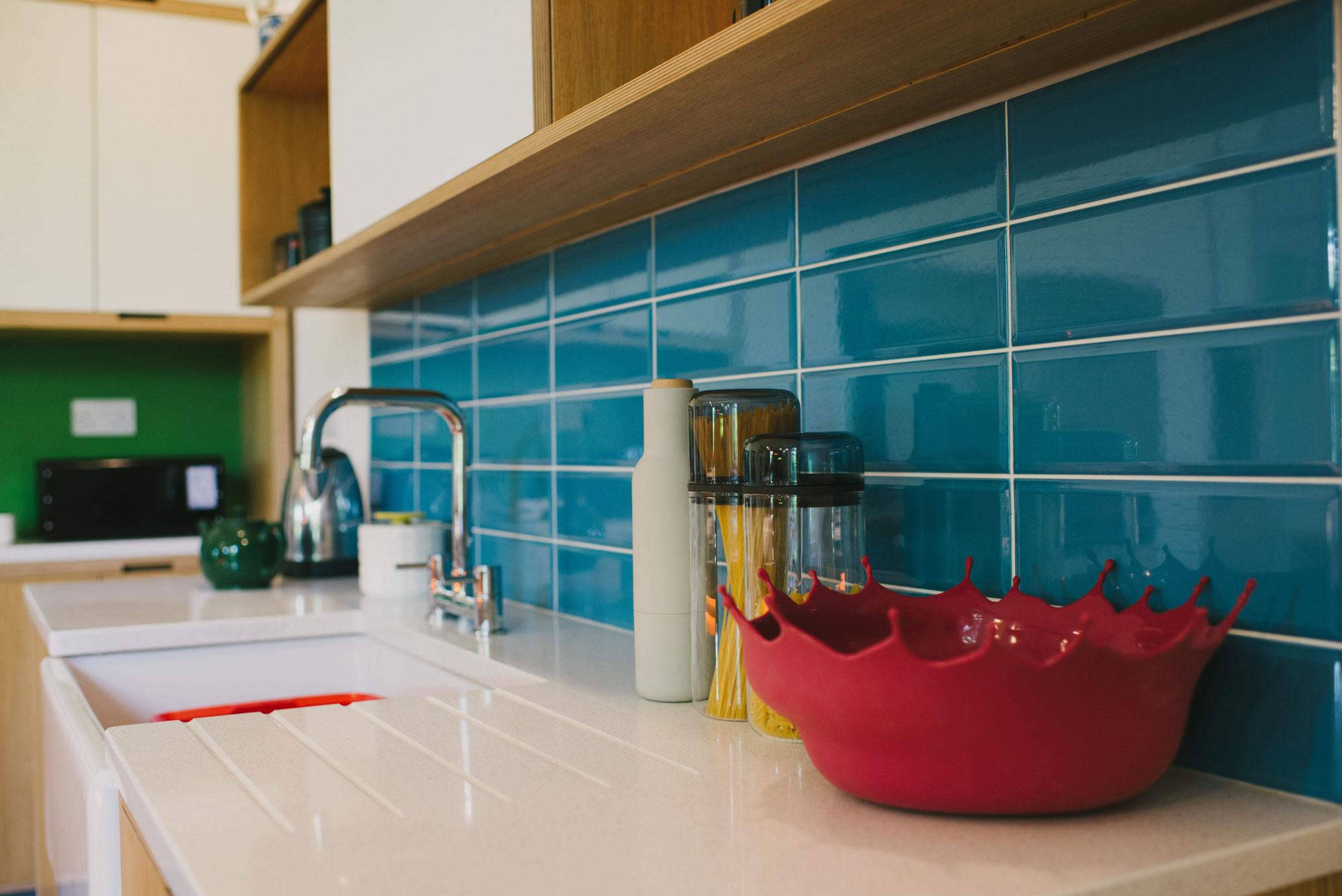 Red Menu drop bowl on white Corian kitchen worktop