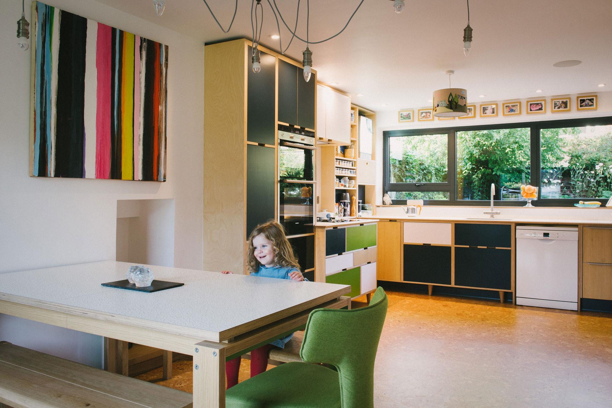 Little girl smiling in bespoke plywood kitchen