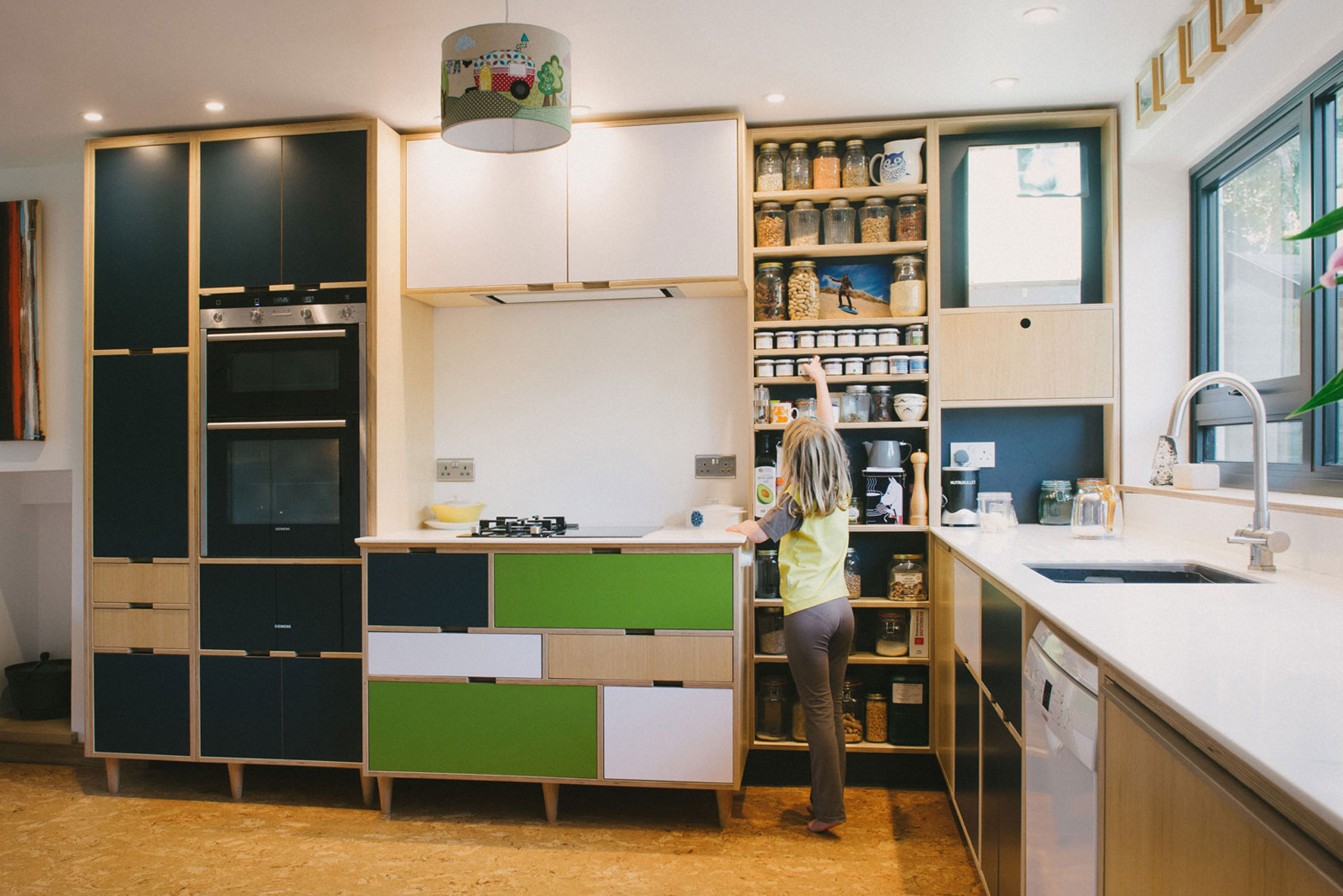 Little girl reaching for spices in green plywood kitchen