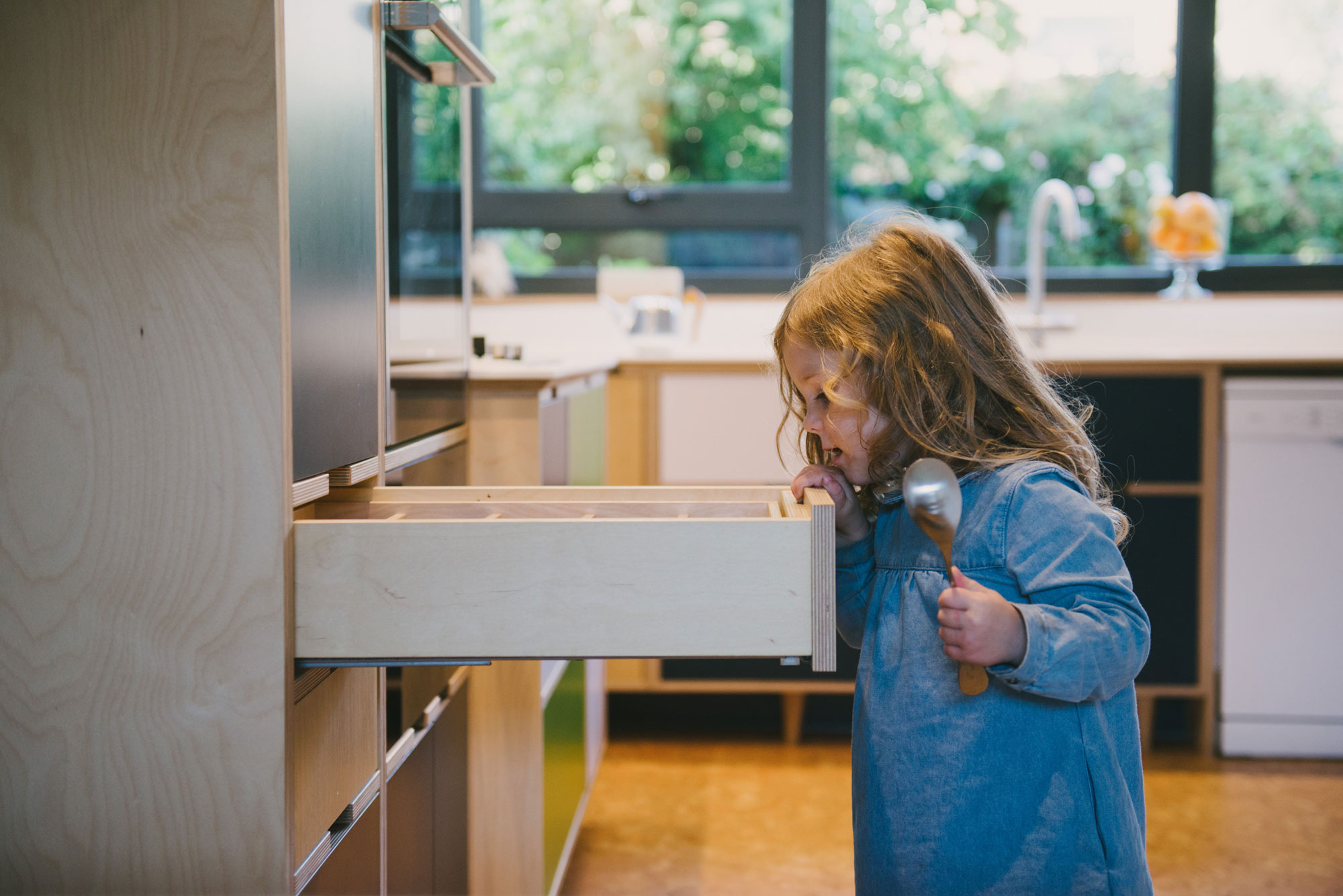 Little girl with spoon looking into plywood drawer