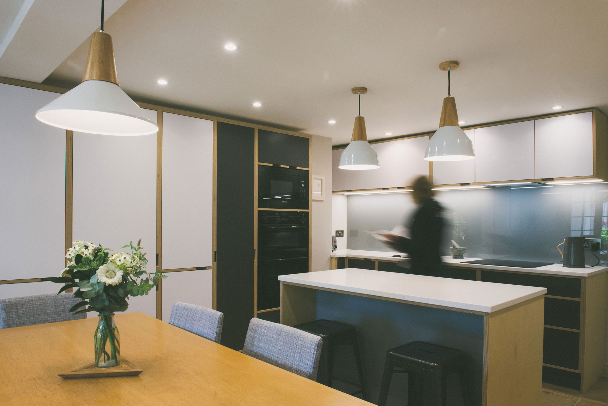 Woman moving across a grey and white plywood kitchen