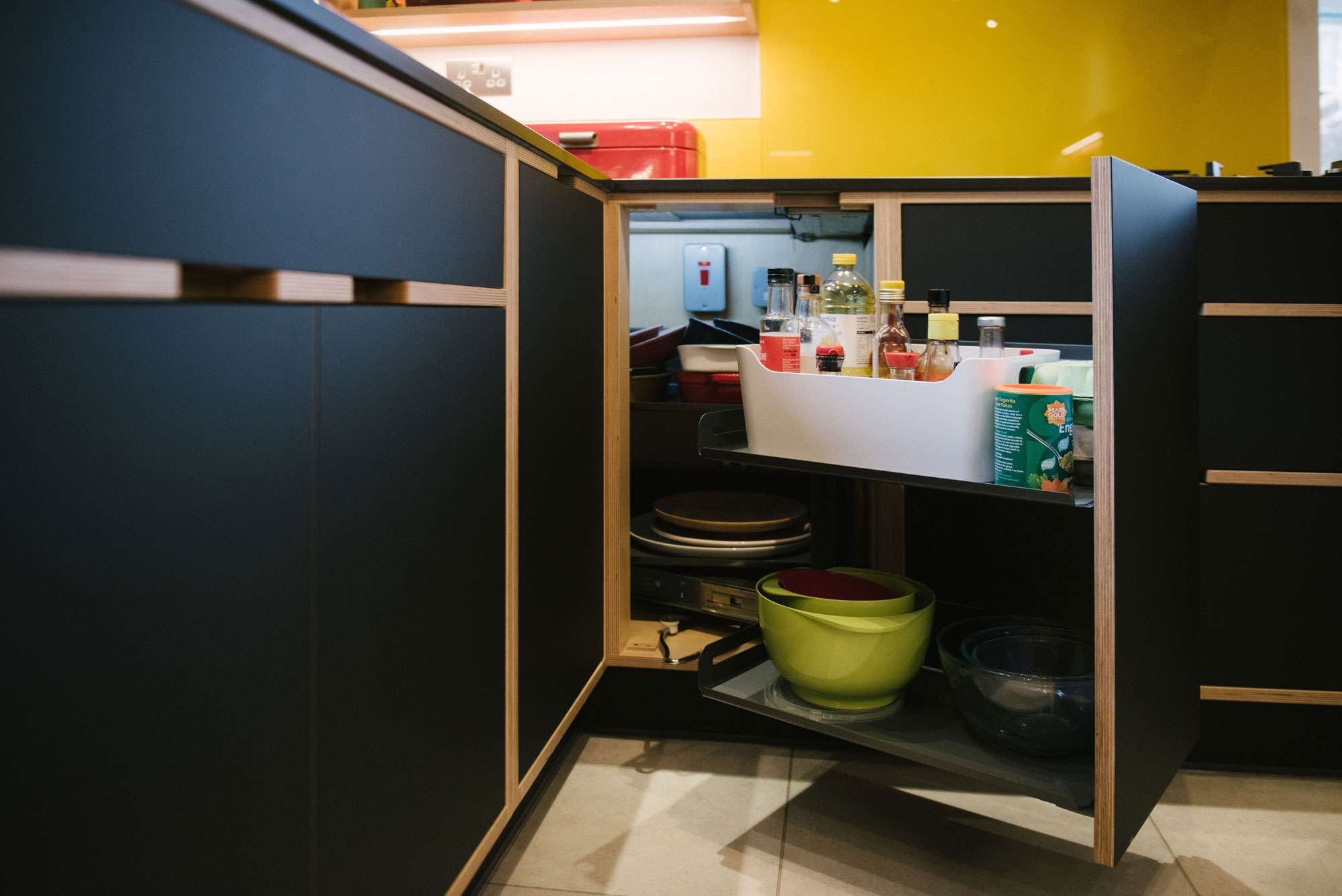 Pull Out Cupboard of Black Plywood Kitchen with Yellow Splashback