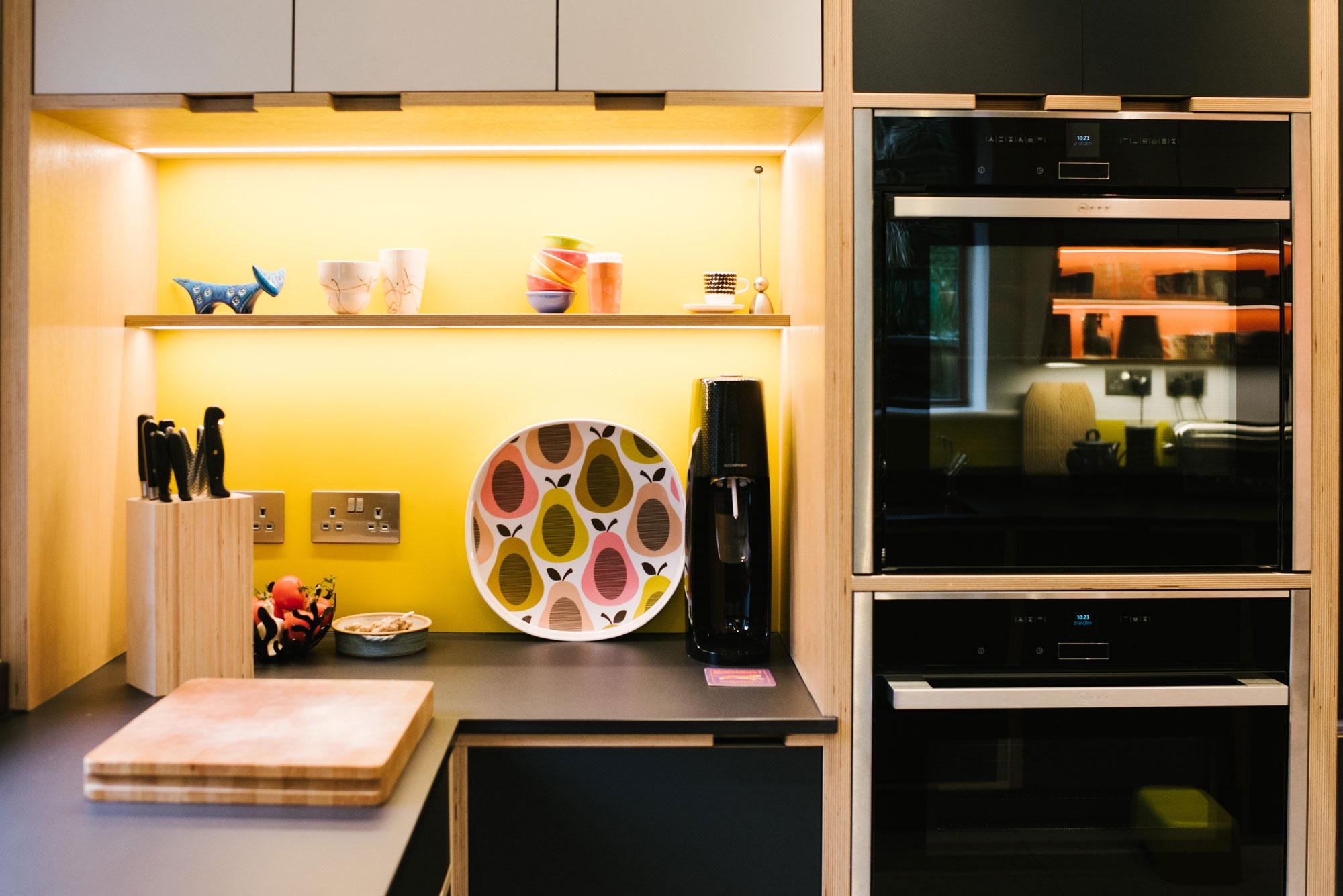 Illuminated Shelving of Black Plywood Kitchen with Yellow Splashback