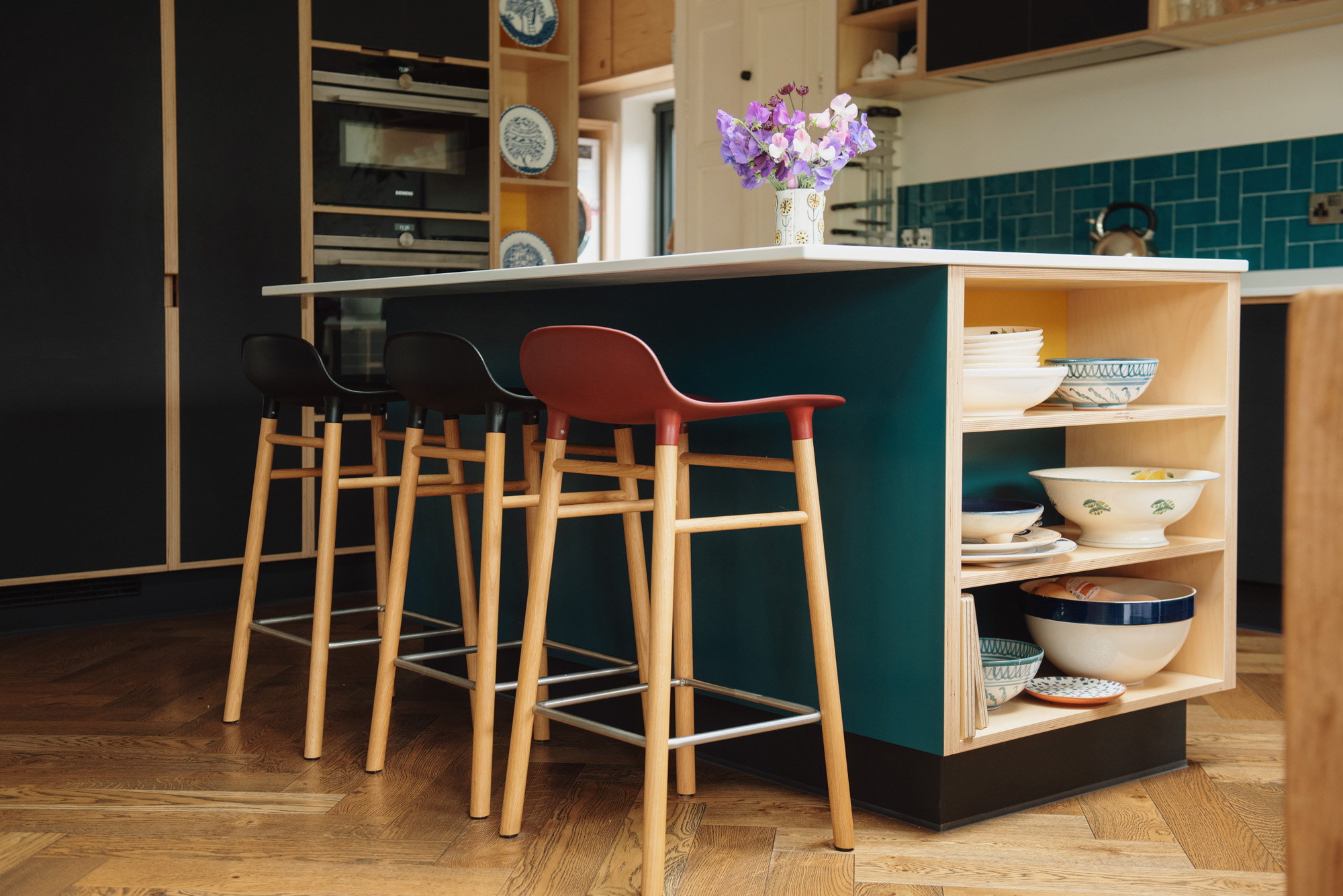 Open sided kitchen island with red and black bar stools