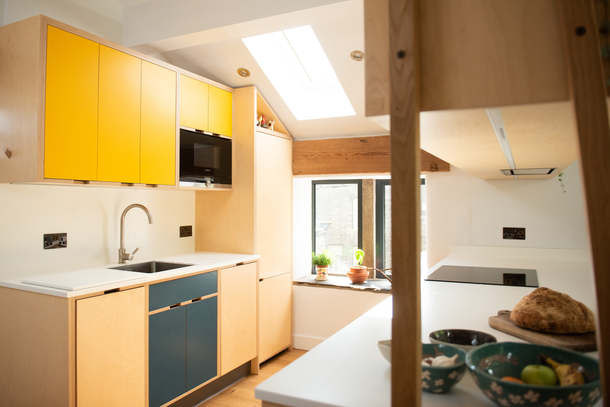 yellow and blue plywood kitchen in converted barn