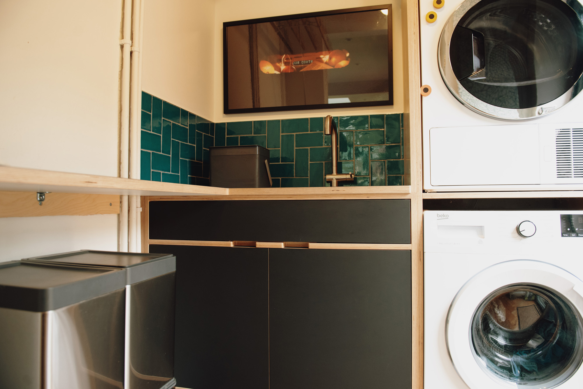 utility room with stacked washer dryer and sink area